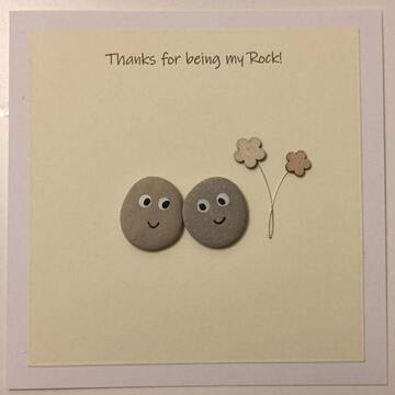 Two googly eye pebbles standing next to flowers, white square background on yellow card -  Size: 6x6 - Greeting: Thanks for being my rock
