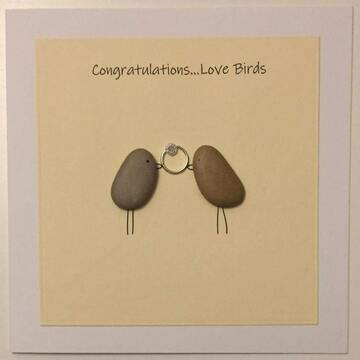 Two pebble birds holding a ring in beak, yellow square background on white card -  Size: 6x6 - Greeting: Congractulations love birds