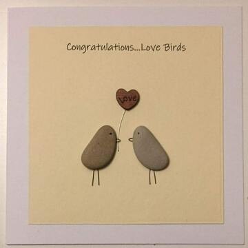 Two pebble birds holding a flower in beaks, yellow square background on white card -  Size: 6x6 - Greeting: Congractulations love birds