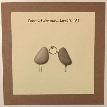 Two pebble birds holding a ring in beak, yellow square background on brown kraft card -  Size: 6x6 - Greeting: Congractulations love birds