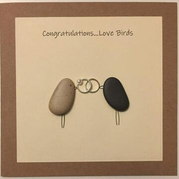 Two pebble birds holding two rings in beak, yellow square background on brown kraft card -  Size: 6x6 - Greeting: Congractulations love birds