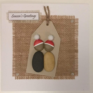 A pebble couple with xmas hats kissing, kraft tag on a hessian square, white background on white card -  Size: 6x6 - Greeting: Season's Greetings